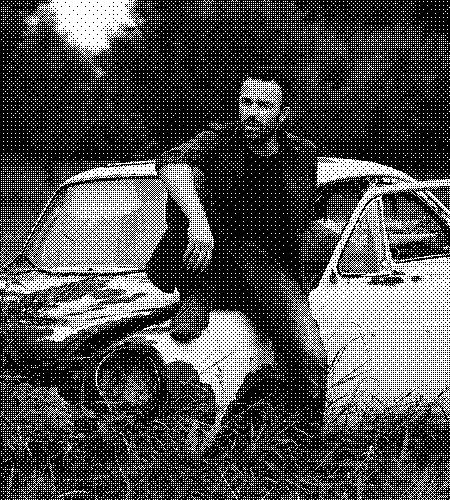 image of a younger man sitting on a car